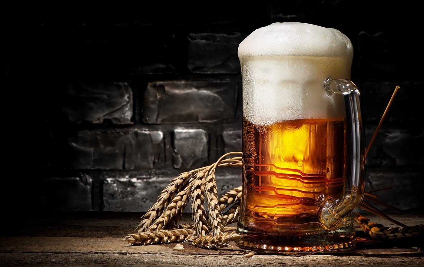 picture of a large mug of light beer on a wooden table with wheat next to it and black in the background